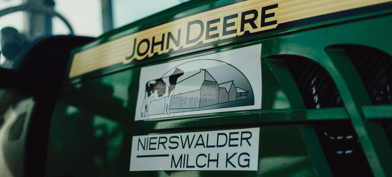 John Deer und Logo Nierswalder Milch KG